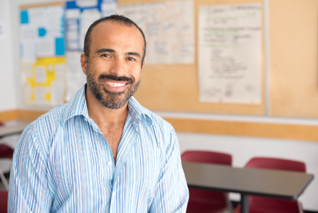 man smiling while appearing to be in a classroom